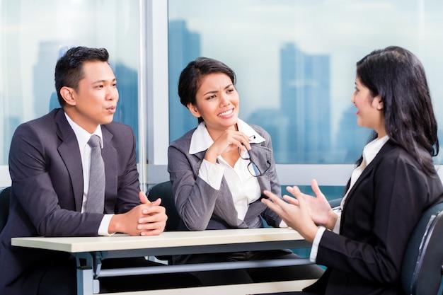 Equipo de reclutamiento asiático que contrata a un candidato en una entrevista de trabajo