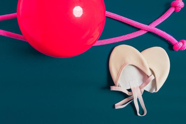 Equipo rítmico de qymnastic. rosa cuerda de saltar, pelota y zapatos de gimnasia aislados en azul