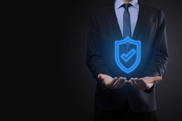 Equipo de seguridad de red de protección en manos de un empresario. concepto de negocio, tecnología, seguridad cibernética e internet - empresario presionando el botón de escudo en pantallas virtuales protección de datos.