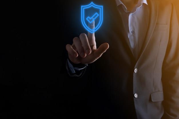 Equipo de seguridad de red de protección en manos de un empresario. concepto de negocio, tecnología, seguridad cibernética e internet - empresario presionando el botón escudo en pantallas virtuales protección de datos.