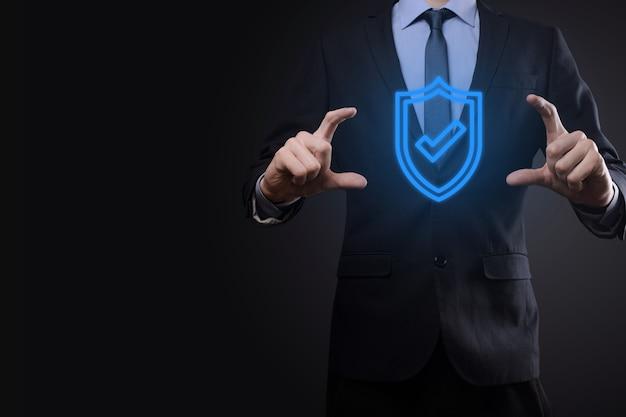 Equipo de seguridad de red de protección en manos de un empresario. concepto de negocio, tecnología, seguridad cibernética e internet - empresario presionando el botón escudo en pantallas virtuales protección de datos