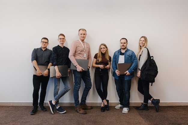 Equipo de seis trabajadores de oficina en pared blanca