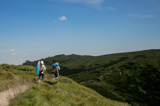 Equipo de senderismo, concepto de trabajo en equipo, equipo exitoso, equipo exitoso de pie en la cima de la montaña, un equipo de escaladores masculinos y femeninos criados.