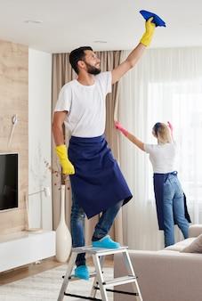 El equipo de servicio de limpieza profesional limpia la sala de estar en un apartamento moderno