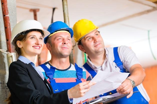 Equipo del sitio de construcción o arquitecto y constructor o trabajador con cascos controlando o discutiendo el plan o anteproyecto