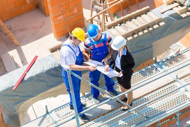 El equipo del sitio de construcción o el arquitecto y el constructor o el trabajador con cascos discuten sobre un plan de construcción de andamios o un anteproyecto o una lista de verificación