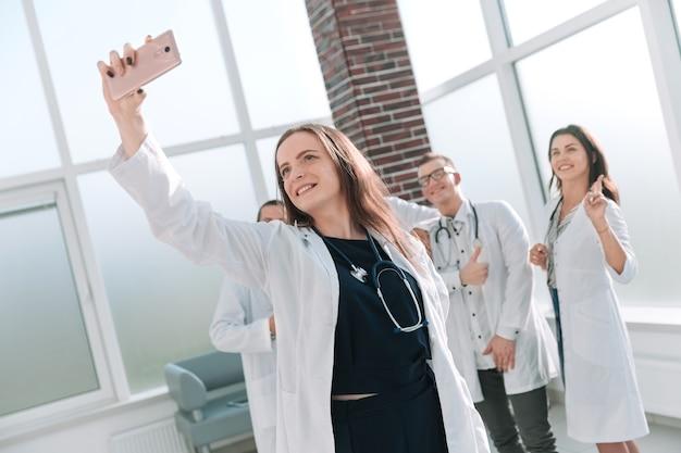Equipo sonriente de médicos en el centro médico tomando un selfie