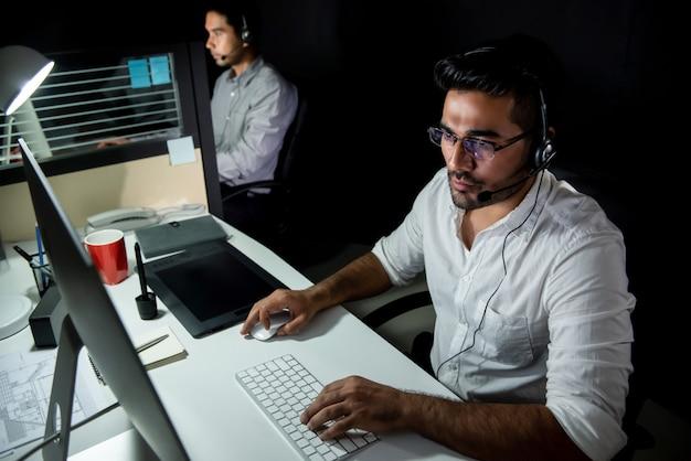 Equipo de soporte técnico asiático trabajando turno nocturno en call center