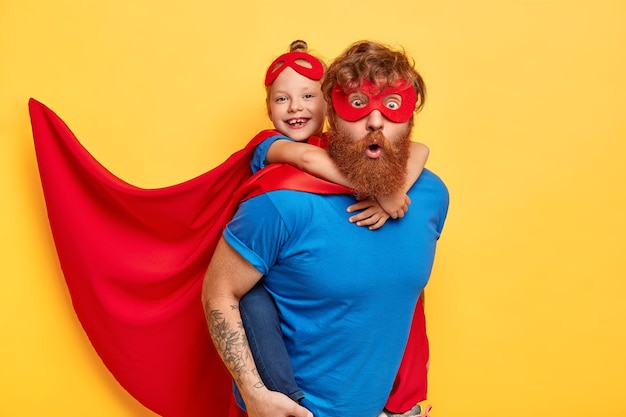 Equipo de superhéroes listo para salvar nuestro mundo. niña pequeña cabalga detrás de su padre superhéroe, finge volar, usa capa roja