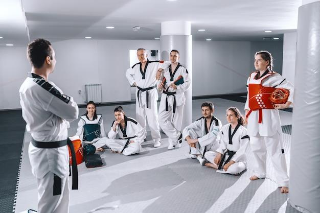 Equipo de taekwondo sentado, de pie y escuchando al entrenador.
