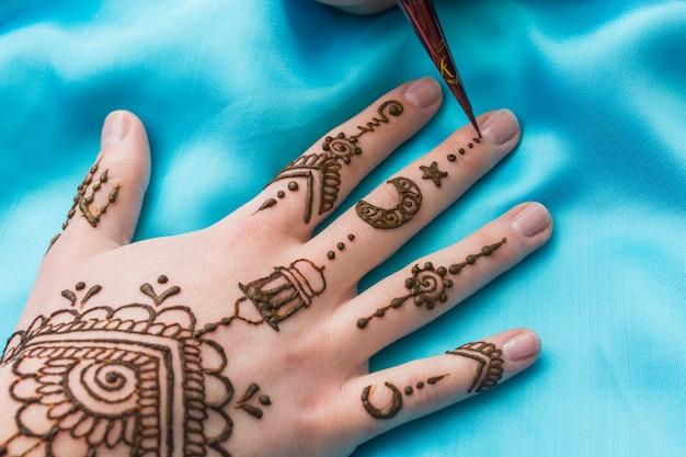 Equipo para tatuar mehndi se acerca a mano de mujer.