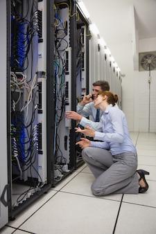 Equipo de técnicos de rodillas y mirando a los servidores.