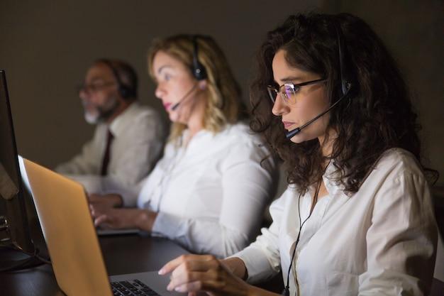 Equipo de teletrabajadores que trabajan en oficinas oscuras