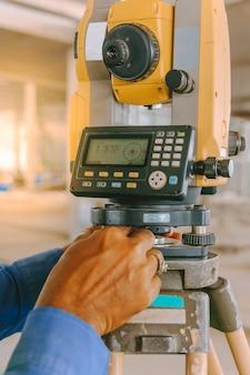 Equipo de topógrafo taquimétrico o teodolito al aire libre en el sitio de construcción