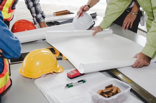 Equipo del trabajador de construcción que planea sobre plan de construcción con el modelo, casco de seguridad