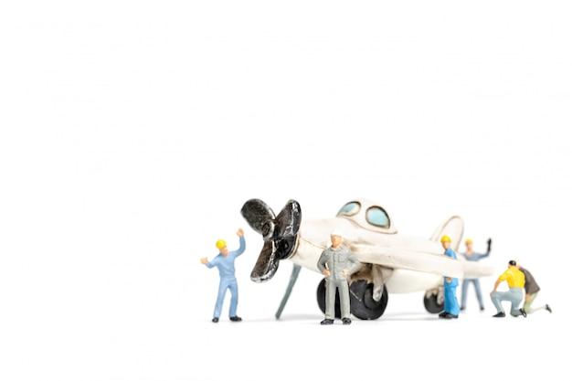 Equipo del trabajador que repara el aeroplano del juguete en el fondo blanco