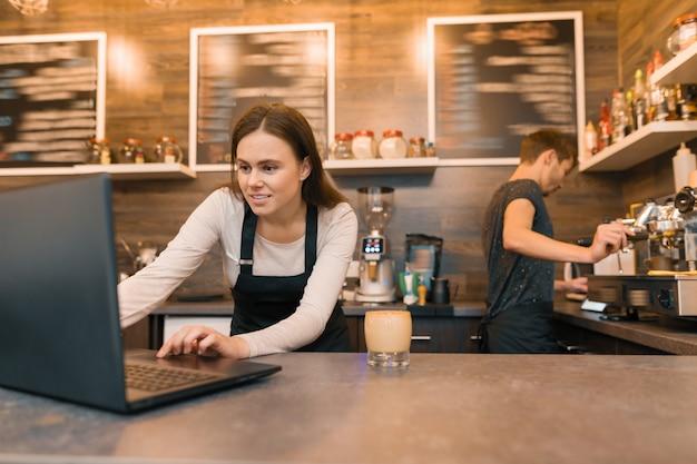 Equipo de trabajadores de la cafetería trabajando cerca del mostrador con una computadora portátil y haciendo café.