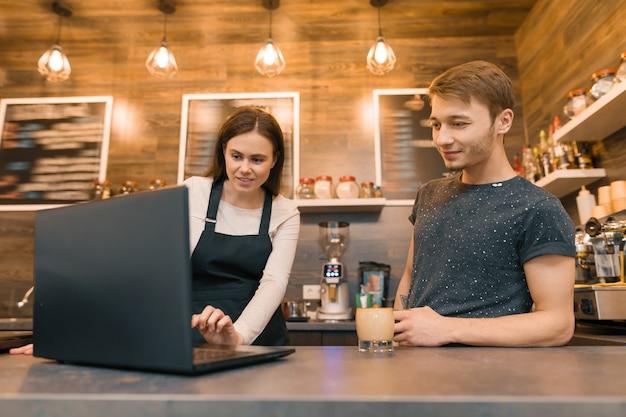 Equipo de trabajadores de cafeterías trabajando cerca del mostrador con laptop