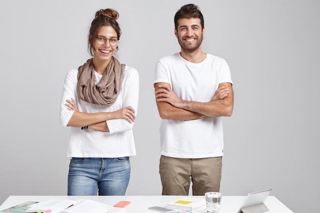 Equipo de trabajadores creativos: hermosa mujer sonriente usa bufanda y grandes gafas y el hombre barbudo mantiene las manos juntas