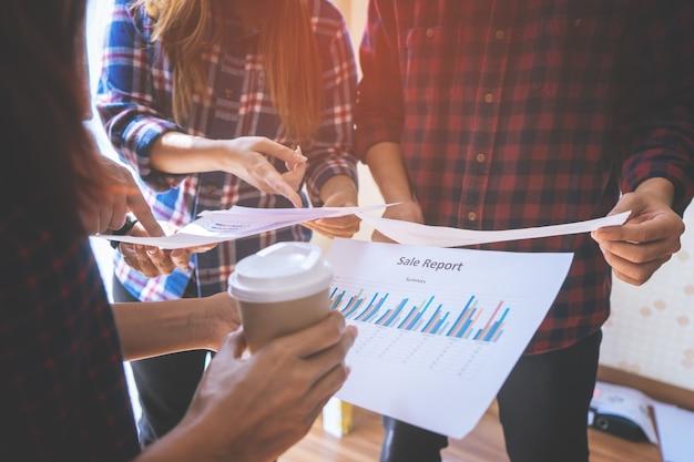 El equipo está trabajando juntos analizando datos de negocios.