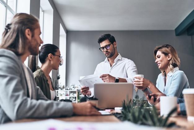 Equipo trabajando juntos. grupo de jóvenes modernos en ropa casual elegante discutiendo negocios mientras trabaja en la oficina creativa