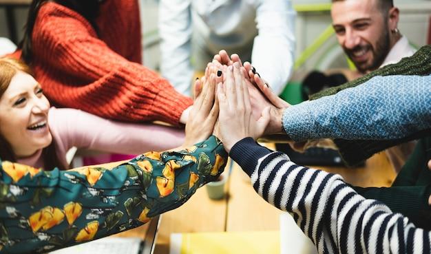 Equipo de trabajo joven que celebra el nuevo inicio en la oficina creativa