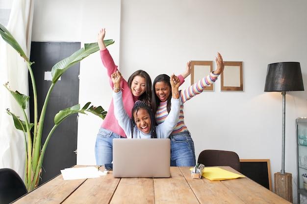 Un equipo de trabajo de mujeres jóvenes celebra las buenas noticias frente al grupo multiétnico de computadoras.