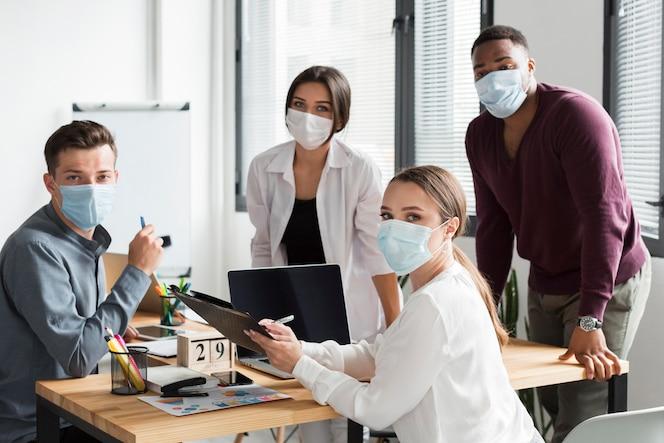 Equipo de trabajo en la oficina durante la pandemia con máscaras faciales