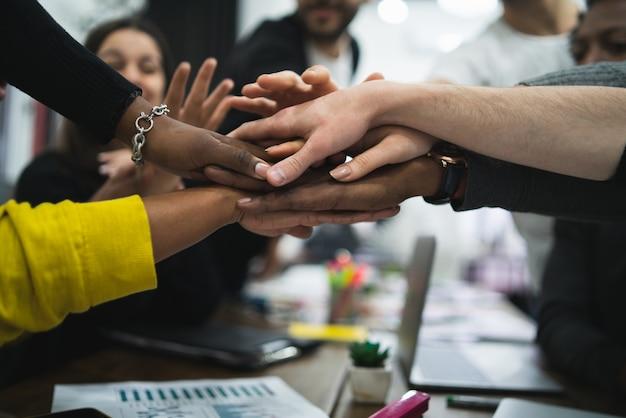 Equipo de trabajo que muestra la unidad con sus manos juntas.