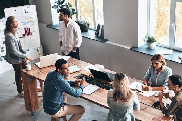Equipo en el trabajo. vista superior de los jóvenes modernos que se comunican mientras trabajan juntos en la sala de juntas