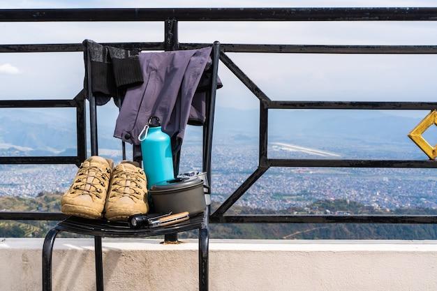 Equipo de trekking o excursionismo: botas, calcetines, pantalones, cuchillo plegable, termo de agua, hervidor de agua y linterna. concepto de actividad al aire libre. naturaleza muerta foto de stock de cerca.