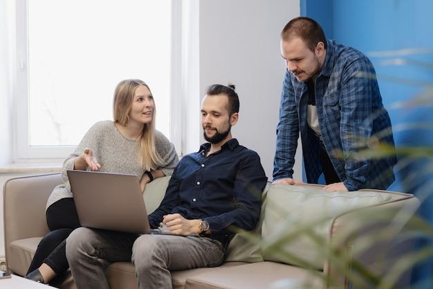 Equipo de tres personas que trabajan en la computadora portátil en la oficina en el sofá