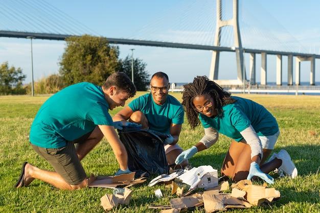 Equipo voluntario feliz que limpia área verde de la ciudad