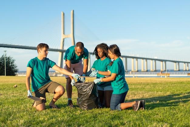 Equipo voluntario multiétnico quitando basura de la hierba