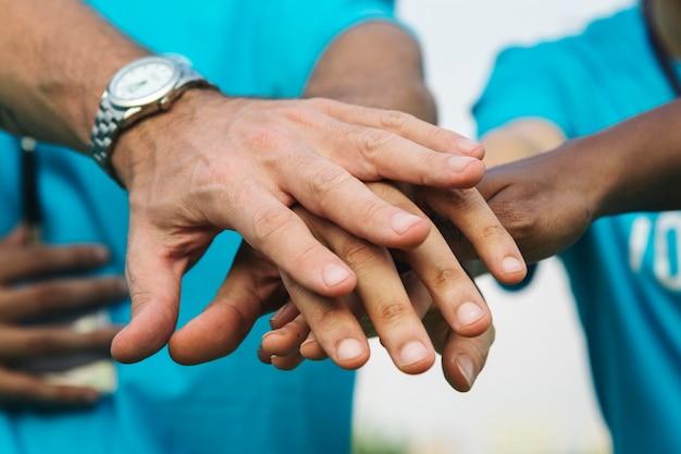Equipo de voluntarios apilando las manos