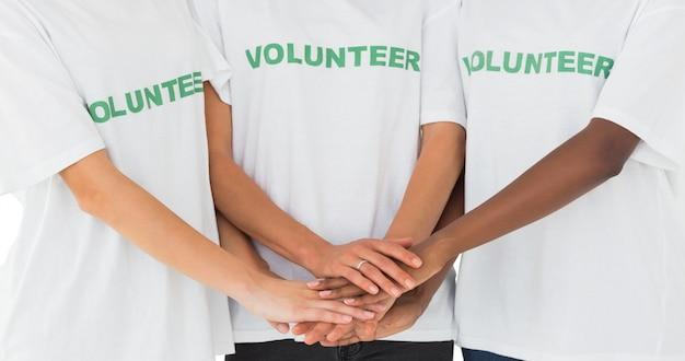 Equipo de voluntarios juntando las manos