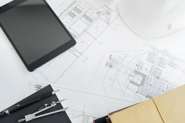 Equipos de construcción. trabajo de reparación. dibujos para la construcción proyecto arquitectónico, rollos de planos y compás divisor en la mesa. concepto de herramientas de ingeniería con espacio de copia.