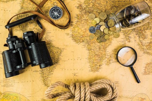 Equipos de viaje y jarra de vidrio con monedas en el mapa de la vendimia