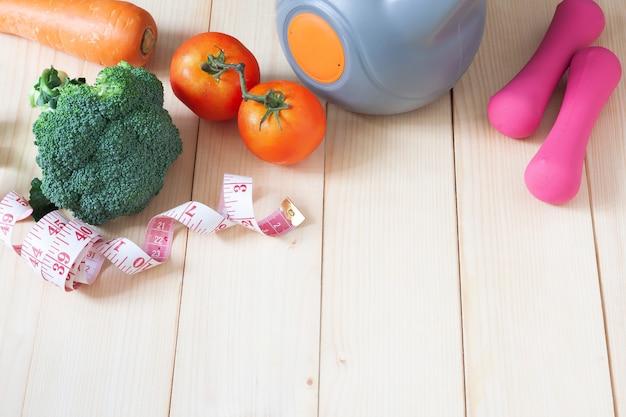 Equipos de deporte y fitness y verduras en la mesa de madera