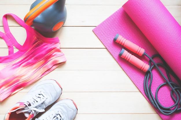 Equipos de fitness y ropa en tono rosa.