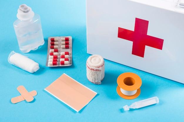 Equipos médicos con botiquín de primeros auxilios sobre fondo azul