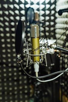 Equipos profesionales con micrófono y amortiguador están en el estudio de música.