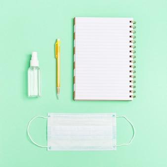 Equipos de protección personal y cuaderno, bolígrafo, caretas y desinfectante para manos