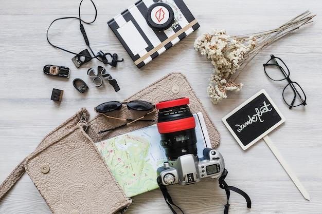 Equipos de viaje y cartel de wanderlust en el escritorio de madera