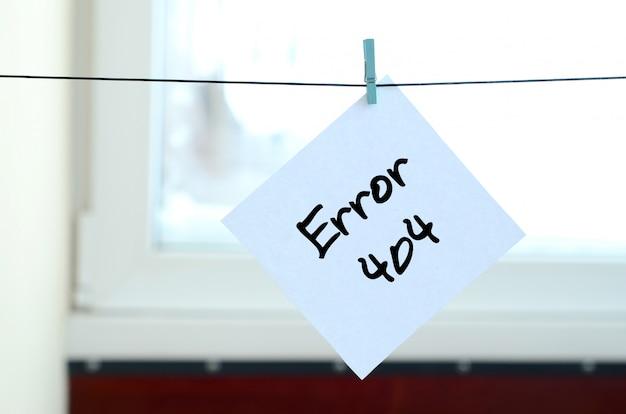 Error 404. la nota está escrita en una pegatina blanca que cuelga con una pinza de ropa en una cuerda