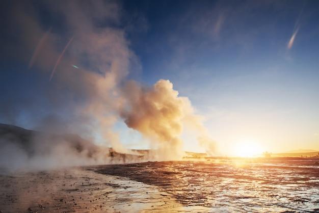 Erupción del géiser strokkur en islandia. colores fantásticos brillan a través del vapor. hermosas nubes rosadas en un cielo azul