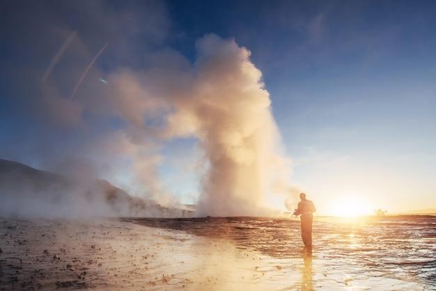 Erupción del géiser strokkur en islandia. colores fríos de invierno, luz del sol a través del vapor