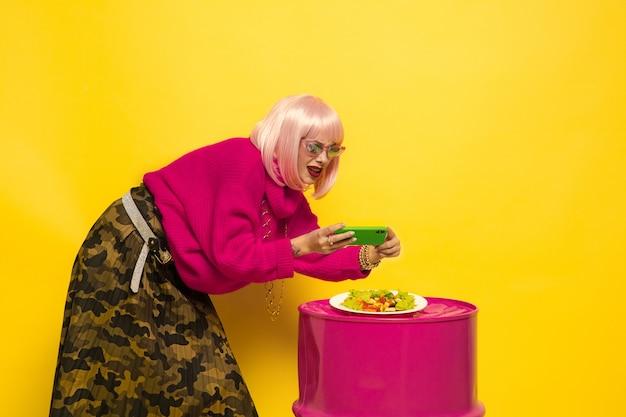 Es difícil ser influyente. selfie primero, comiendo después. necesito un plato antes. retrato de mujer caucásica en amarillo. hermosa modelo rubia. concepto de emociones humanas, expresión facial, ventas, publicidad.