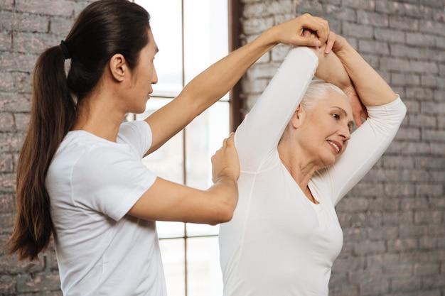 Es fácil. atractiva mujer de jubilación sosteniendo su espalda recta mientras estira su brazo derecho de pie cerca de su instructor