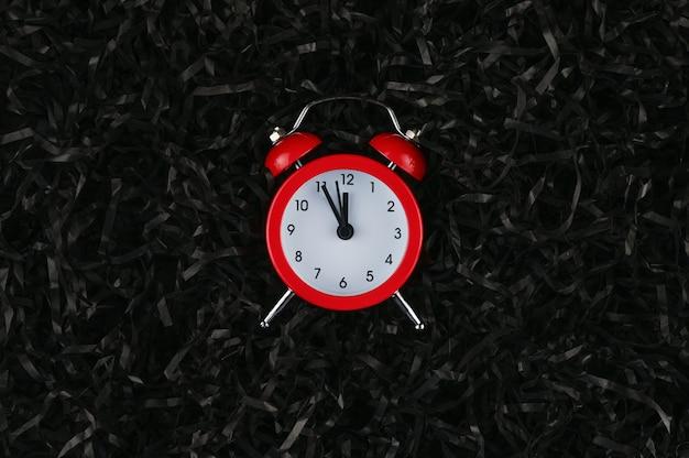 Es hora de celebrar la navidad y el año nuevo, reloj despertador sobre papel.